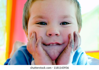 Close up portrait of a toddler boy with a dirty face and hands