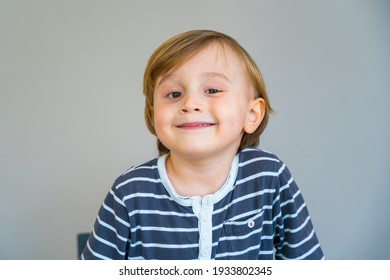 Close up portrait of a toddler boy of two years old indoor. Happy child wearing striped t shirt looking at the camera smiling with pleasure