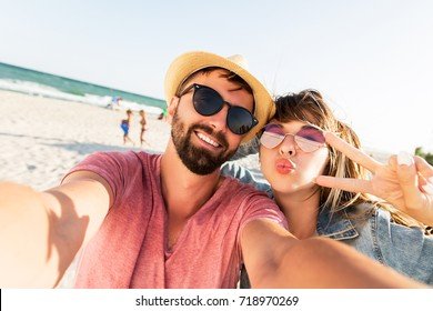 Close up portrait of  travel couple make  selfie of their trip, positive moments.  Crazy self portrait. Straw hat, stylish sunglasses, windy hairs.