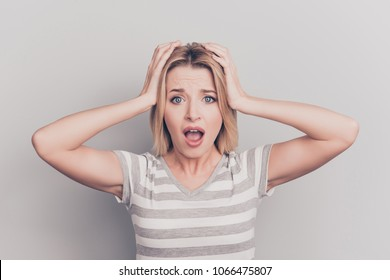 Close up portrait of troubled frightened crazy terrified shocked beautiful amazed with open mouth woman holding head with hands wearing casual outfit isolated on gray background copy-space