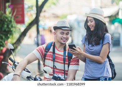 close up portrait of two backpackers with summer hat seeing the result of their photo on mobilephone