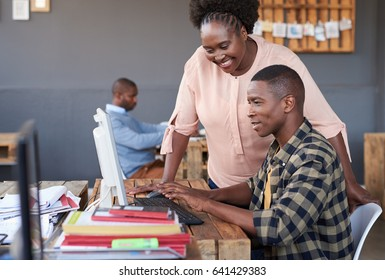 Close up portrait of two casually dressed young African business coworkers using a computer and talking together, while working at a table in a modern office