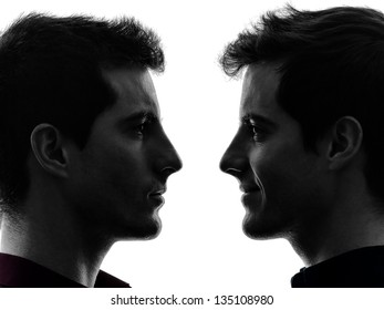 close up portrait  two caucasian young men in shadow  white background
