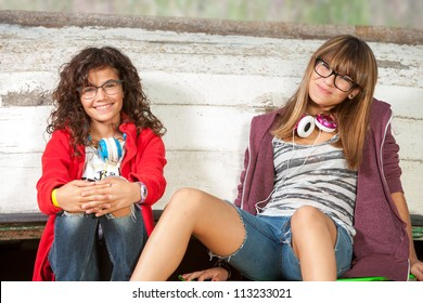 Close up portrait of two cute teenage girlfriends sitting outdoors.