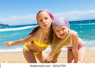 Close up portrait of two girlfriends in swimwear on beach.