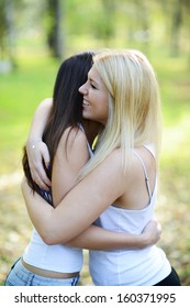 Close up portrait of two happy girls hugging outdoors