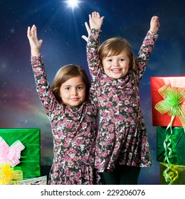 Close up portrait of two happy young sisters raising hands next to gifts. Studio portrait with winter background.