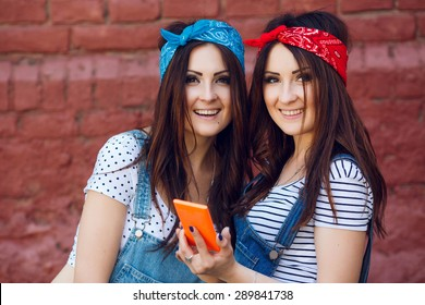 Close up portrait of two happy young twins girls with orange smart phone. Wearing bright bandanas. On a brick urban wall background.