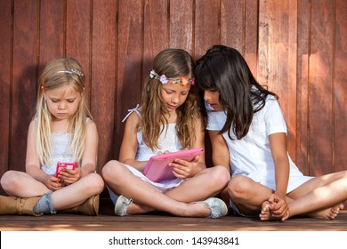 Close up portrait of two kids with tablet and smart phone outdoors.