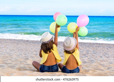 Close up portrait of two little girls sitting with balloons on beach.Rear view of kids in casual wear and wearing hats.