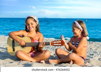Close up portrait of two little girls singing together with guitar on beach.
