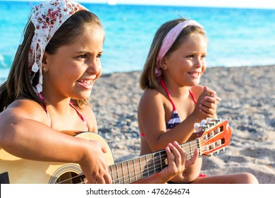 Close up portrait of two Little girls having fun singing with guitar on beach.