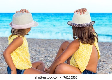 Close up portrait of two little girls wearing hats sitting together on beach.Rear view of Kids looking at sea.