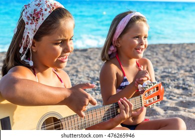 Close up portrait two little girls wearing headbands singing together on beach. One girl playing guitar and other in background clapping hands.