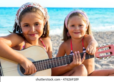 Close up portrait of two little girls having fun with guitar on beach.