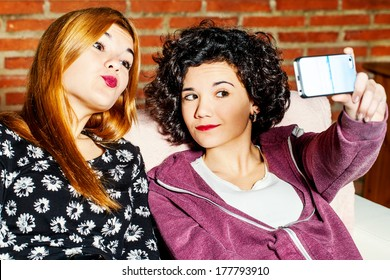 Close up portrait of two teen girls taking auto portrait with smart phone.