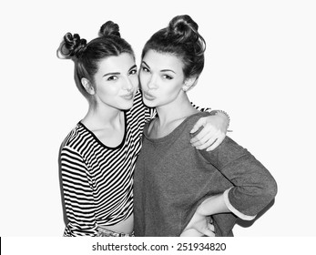Close up portrait of two young girl having fun and hugging. Top knot hairdo. White background, not isolated. Inside
