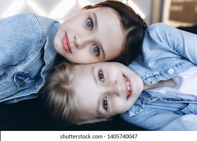 Close up portrait of two young girls blondie and drownie in jeans jackets on bed smiling. Fashion, beauty, happiness concept