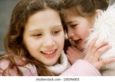 Close up portrait of two young girls children sisters in a park during a cold winter day, with one whispering secrets into the others ear, smiling and laughing outdoors.