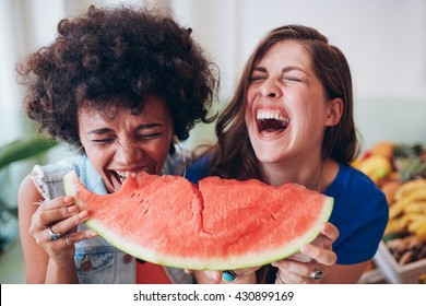 Close up portrait of two young girls enjoying a watermelon. Female friends eating a watermelon slice and laughing together.