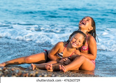 Close up portrait of two youngsters having fun together in waves.