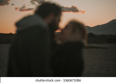Close up portrait of unfocused couple kissing at sunset with an orange sky in the background, and a plane flying between their faces.