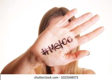 Close up portrait of unknown young woman covering her face w/ #Metoo hashtag word on palm of hand isolated on white. Me too movement. Anti sexism protest against inappropriate behavior towards women.