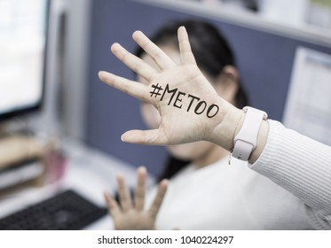 Close up portrait of unknown young woman covering her face w/ #Metoo hashtag word on palm of hand, taken in the office. Me too movement. Anti sexism protest against inappropriate behavior towards wome