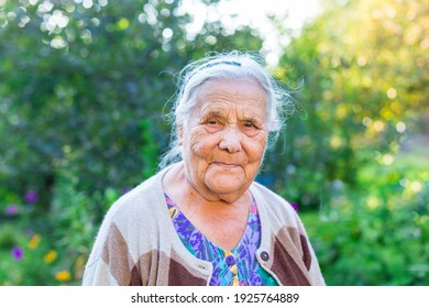 Close up portrait of a very old wrinkled woman of eighty or ninety years old, looking at the camera, staying in her garden. Old age and lifestyle concept. Aging process.