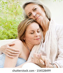 Close up portrait view of a mature mother and her adult daughter hugging and cuddling giving family support and comfort while relaxing on a white sofa at home.