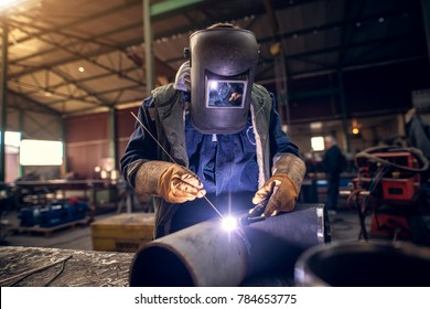 Close up portrait view of professional mask protected welder man in uniform working on the metal sculpture at the table in the industrial fabric workshop in front of few other workers.