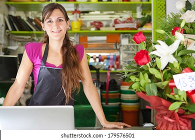 Close up portrait of a welcoming florist business woman owner proudly standing at her flower shop counter using a laptop computer and smiling. Small business technology.