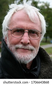 Close up portrait of white bearded senior with glasses and long black leather coat standing outside in a park