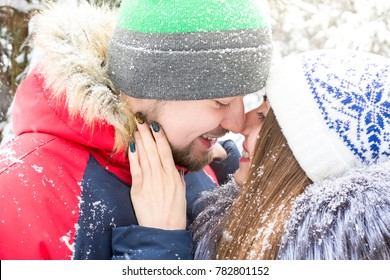 Close up portrait of winter couple that kissing under snowfall in the forest among the christmass trees. Emotional winter promotion background for banner or advertising. Red blue and white colors.