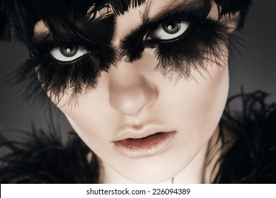 close up portrait woman with black feathers on eyes