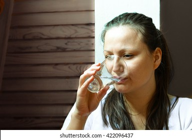 Close up portrait of woman drinking the water on the dark gray background