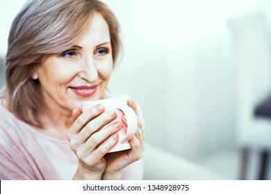 A Close Up Portrait of a Woman of European Appearance. In Appearance Woman are Over 50 Years Old. There is a Smile on Her Face. The Woman Has in Hands Cup with Coffee.