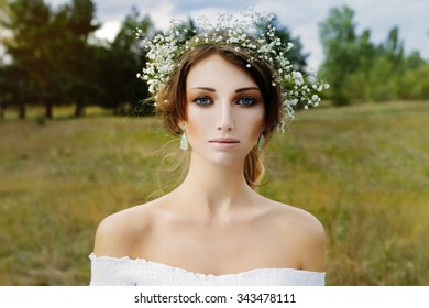 Close up portrait of woman face wearing floral white wreath outdoors