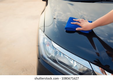 Close up portrait of woman hand cleaning front grille a car. Car care and maintenance concept.