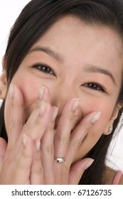 Close up portrait of woman with hands in front of mouth