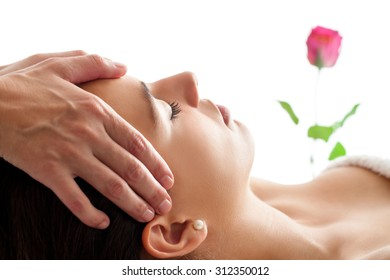 Close up portrait of Woman having Facial massage. Therapist doing head massage  isolated against white background.