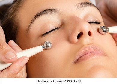 Close up portrait of woman having Galvanic facial treatment with low level current electrodes.