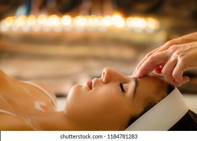 Close up portrait of woman having head massage in spa. Low key atmosphere with out of focus candles glowing in background. Therapist touching girl's forehead.