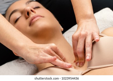 Close up portrait of woman having kinesiological therapy. Hands applying pressure on chest.