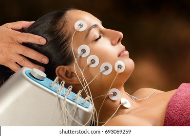 Close up portrait of woman having skin tightening treatment with low frequency electrodes. Hypo allergenic pads placed on womanâ??s face.