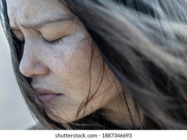A close up portrait of a woman with her eyes closed in deep depression and sadness, staning in the cold winter day.