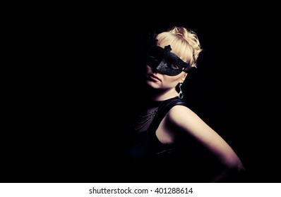 Close up portrait of woman in mysterious mask over black background