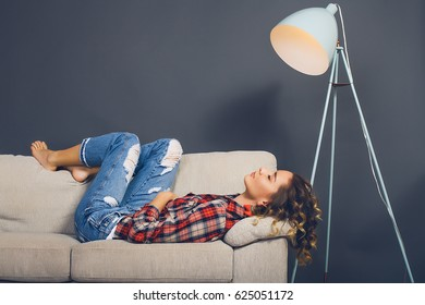 Close up portrait woman sleeping on couch.indoor portrait,young girl hipster with curly hair,woman in plaid shirt,Wonderful mood,make up artist,grey background,relax time,beautiful tan,girl at home
