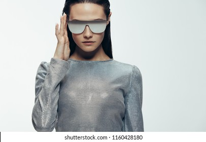 Close up portrait of woman in sliver outfit and mirrored sunglasses looking at camera. Stylish female model in robotic look against grey background.