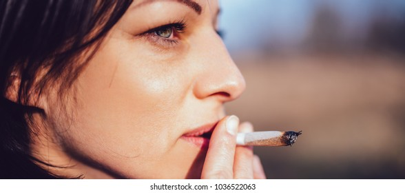 Close up portrait of woman smoking outdoors